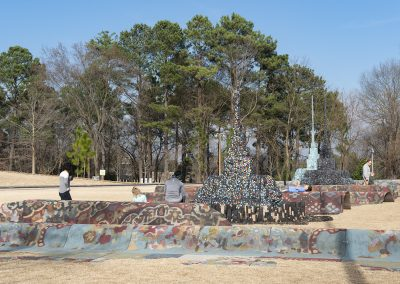 The North Carolina Museum of Art's Ellipse in the Ann and Jim Goodnight Museum Park with visitors interacting with Leonardo Drew's installation, City in the Grass.